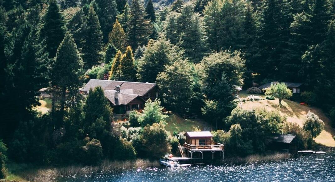 Lago y casas con bosque de fondo en Bariloche.