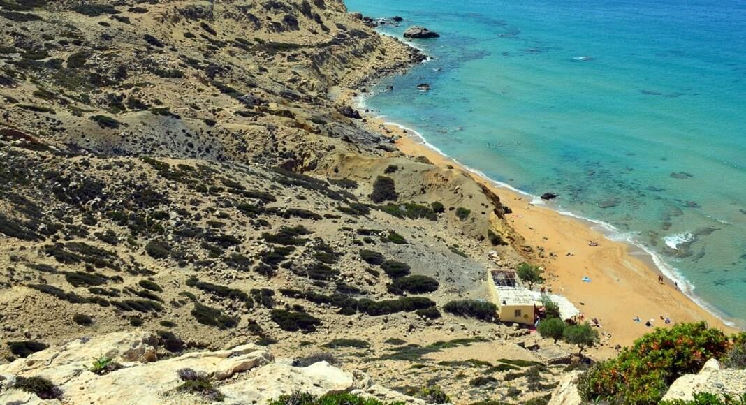 Arena, rocas y mar en Red beach, Grecia.